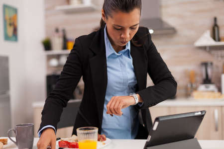 Woman hurrying up to finish breakfast while shes late at the meeting. Young freelancer working around the clock to meet her goals, stressful way of life, hurry, late for work, always on the run