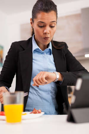 Business woman late at the office while eating toasted bread. Concentrated business woman during breakfast