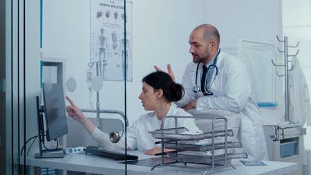 Two doctors consulting over a medical problem over a glass wall while patients and medical staff are walking in hallway. Healthcare system, private modern medical hospital clinic