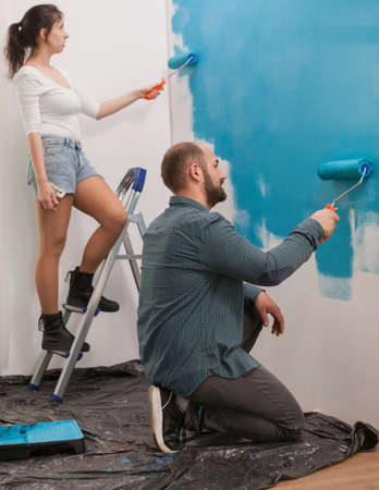 Wife using the ladder helps her husband to paint apartment wall using roller brush. Apartment redecoration and home construction while renovating and improving. Repair and decorating