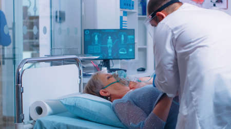 In modern hospital or clinic doctor is putting oxygen mask on senior patient who lies in bed. Coronavirus covid-19 related medical medicinal healthcare theme. Infection treatment during epidemic Standard-Bild