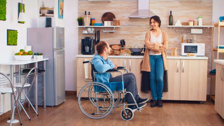 Woman smiling at disabled husband in wheelchair while talking with him.