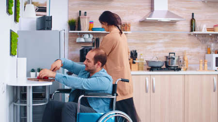 Disabled man in wheelchair chopping bell pepper in kitchen helping wife to cooking delicious meal.
