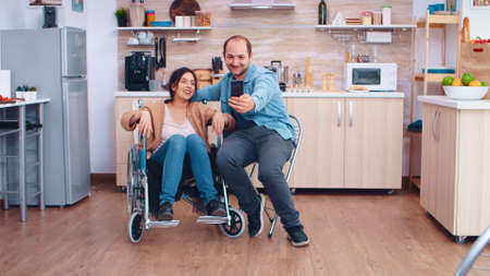 Positive woman in wheelchair and husband taking a selfie in kitchen using smartphone.