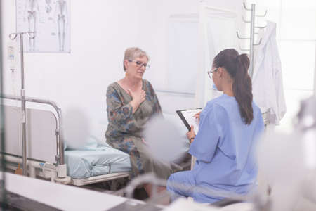 Senior patient discussing about illness with nurse during medical examination in hospital office.