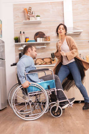 Disabled man in wheelchair singing with his wife in kitchen. Young couple having fun. Stock fotó