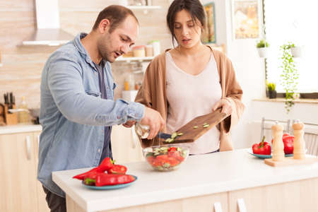 Man pouring olive oil on salad in kitchen. Healthy salad with fresh vegetables.