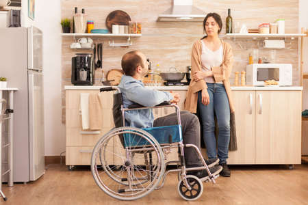 Disabled man in wheelchair having a conversation with wife in kitchen while preparing food. Disabled paralyzed handicapped man with walking disability integrating after an accident.