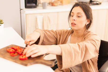 Woman with walking handicap cutting red paper on wooden board in kitchen using sharp knife.