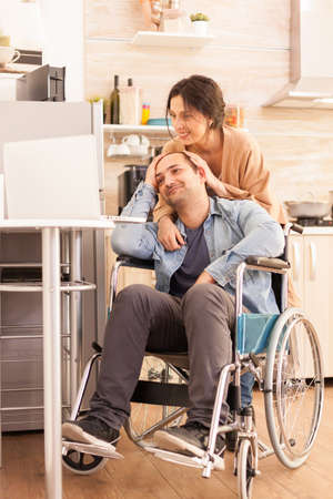 Cheerful disabled man in wheelchair and wife looking at laptop in kitchen.