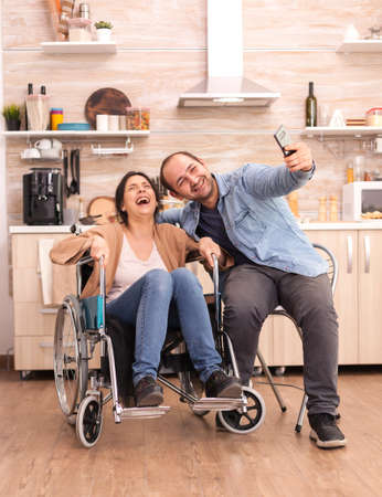 Boyfriend taking selfie with happy and disabled wife in wheelchair.