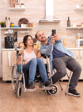Cheerful woman in wheelchair taking photos with husband in kitchen.