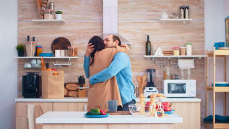 Cheerful couple smiling and dancing in kitchen. Romantic husband and wife. Cheerful happy young family together dance. Fun love affection romance leisure romantic music for enjoynment Imagens