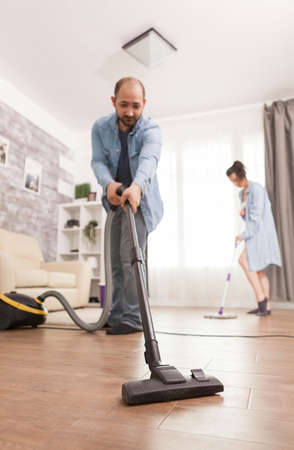 Cleaning floor with vacuum cleaner used by husband. Фото со стока