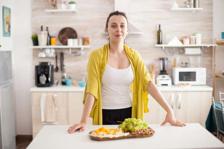 Cheerful wooman looking at camera in home kitchen with delicious variety of cheese and grapes on wooden plate