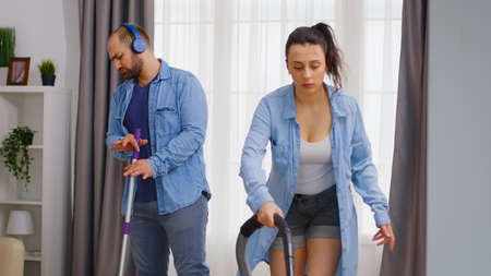 Happy man listening music on headphones and cleaning the floor with mop while his wife is using vacuum cleaner.