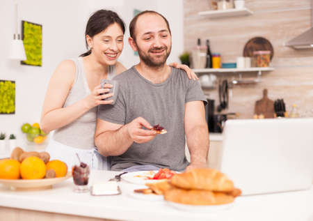 Couple talking online with family on a video call during breakfast. Videoconference in the morning, using online web internet technology, talking and communicating with relatives