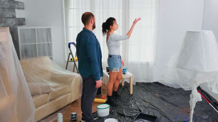 Couple renovating home. Apartment redecoration and home construction while renovating and improving. Repair and decorating.