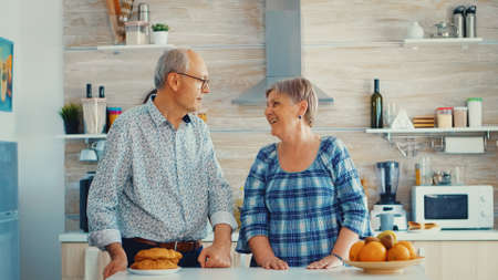 Slow motion portret of senior couple in kitchen smiling at each other and looking at camera. Cheerful wife and husband.
