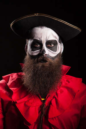 Handsome with a beard dressed up like dangerous pirate for halloween isolated on black background.