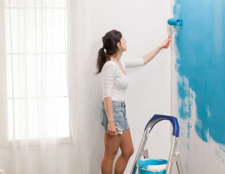 Caucasian woman redecorating apartment and painting walls with roller brush. Apartment makeover. Redecoration and home construction while renovating and improving. Repair and decorating.
