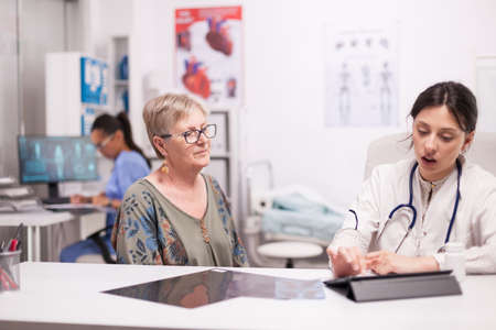 Doctor using tablet computer while examining senior woman in hospital office. Medic discussing diagnosis with patient about her illness.