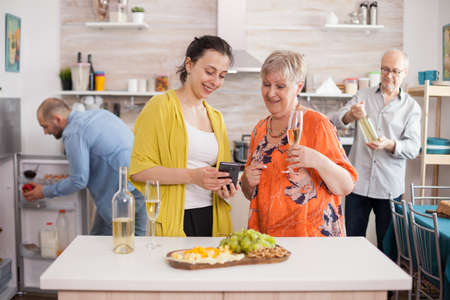 Mother and daughter surfing internet using smarthphone in kitchen during family meeting and drinking wine.