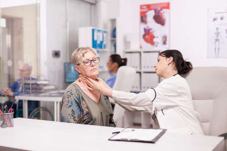 Doctor touching senior patient neck for glands abnormalities in hospital office. Medic examining elderly woman. Stockfoto
