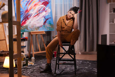 Exhausted painter sitting on chair in art studio with masterpiece behind it. Modern artwork paint on canvas, creative, contemporary and successful fine art artist drawing masterpiece