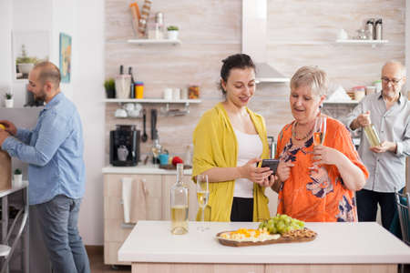 Mother and daughter smiling in kitchen using smarthphone drinking wine.