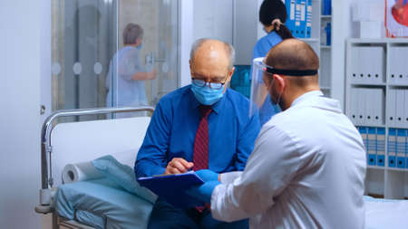 Patient wearing protection mask and signing the discharge form. COVID-19 medical healthcare consultation during global pandemic. Private modern health clinic or hospital, medical medicine treatment