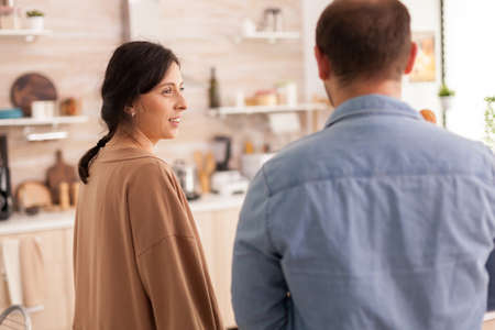 Wife looking at husband in kitchen arriving from supermarket. Healthy happy relationship lifestyle for man and woman, together shopping products Stock Photo