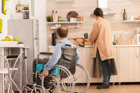 Man with walking handicap in wheelchair looking at wife how shes cooking. Disabled paralyzed handicapped man with walking disability integrating after an accident.