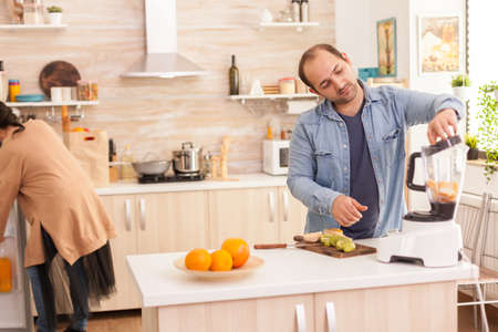 Man mixing fruits in blender while wife is looking inside refrigerator. Healthy carefree and cheerful lifestyle, eating diet and preparing breakfast in cozy sunny morning Reklamní fotografie