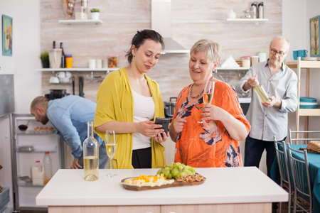 Mother and daughter using smarthphone in kitchen. Senior woman holding glass of wine. Old man looking at bottle.