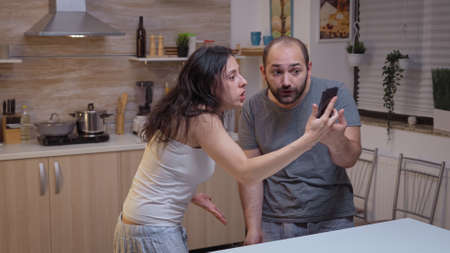 Angry woman yelling at unfaithful man. Jealous wife cheated angry frustrated offended irritated accusing her husband of infidelity showing him messages on smartphone screaming desperate Foto de archivo
