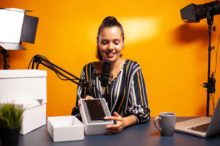 Influencer presenting phone for giveaway during podcast. . Creative content creator influencer expert vlogger recording online internet web podcast gift for audience