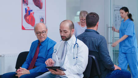 Doctor in white coat with stethoscope discussing diagnosis with old man in hospital waiting area. Nurse helping senior woman with walking frame. Man waiting for medical examination.
