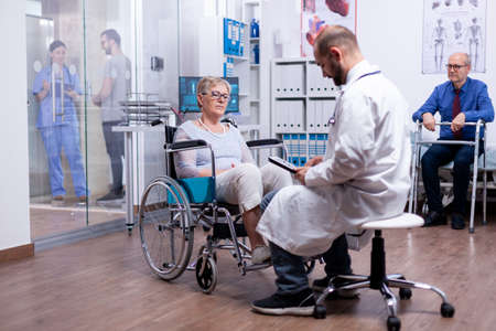 Woman with parkinson sitting in wheelchair in hospital room during medical examination. Man with disabilities ,walking frame sitting in hospital bed. Health care system, clinic patients.
