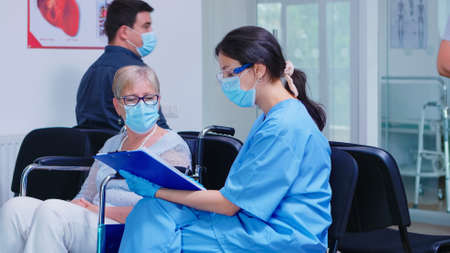 Nurse explaining diagnosis to disabled senior woman in wheelchair. Assistant wearing face mask against infection with coronavirus in hospital waiting area.