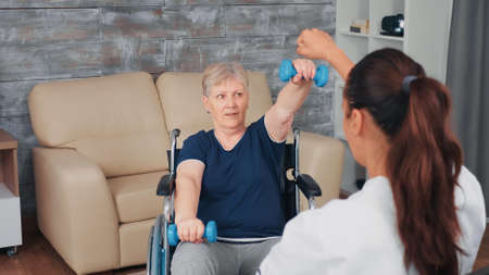 Senior woman in wheelchair doing home rehabilitation training with doctor. Disabled handicapped old person recovering professional help nurse, nursing retirement home treatment and rehabilitation