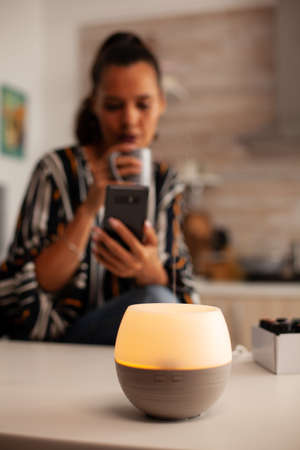 Woman browsing on phone enjoying aromatherapy from essential oil diffuser. Aroma health essence, welness aromatherapy home spa fragrance tranquil theraphy, therapeutic steam, mental health treatment