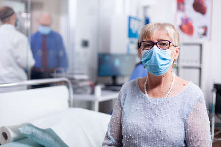 Elderly sick patient with face mask in hospital cabinet waiting for doctor. Global health crisis, medical system during pandemic, sick elderly patient in private clinic.