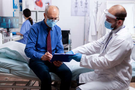 Senior patient with face mask agasint coroanvirus pandemic signing document with health diagnosis in hospital room with doctor. Healthcare medical physician consultation during COVID-19 global crisis.