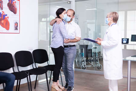 Disappointed young couple in hospital waiting area from doctor unfavorable bad news during coronavirus outbreak. Medic wearing face mask against infection with covid-19. Archivio Fotografico