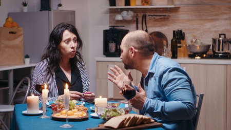 Happy pregnant woman dissapointed by husband during romantic dinner showing positive test. Unhappy, nervous, angry man fighting with wife, unwanted baby, frustrated for results.