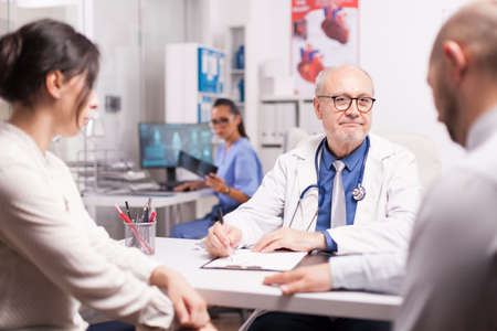 Senior medical practitioner taking notes on clipboard during consultation of married couple in hospital office. Doctor looking at male patient while wearing white coat and stethoscope.