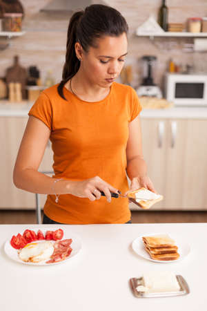 Preparing the sandwich for breakfast spreading butter on roasted bread. Woman spreading butter on toasted bread for breakfast. Knife smearing soft butter on slice of bread. Healthy lifestyle, making morning delicious meal in cozy kitchen. Traditional tasty lunch