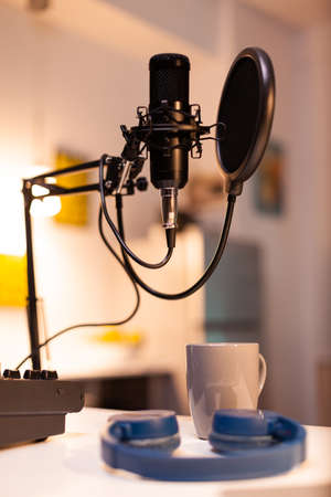 Zooming on professional microphone in vlogger home studio and neon light in the background. Influencer recording social media content with production microphone. Digital web internet streaming station Stok Fotoğraf