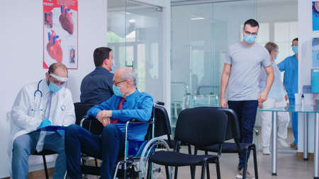 Invalid old man with face mask against infection with coronavirus in wheelchair discussing with doctor in hospital waiting area. Nursing inviting patient in examination room.